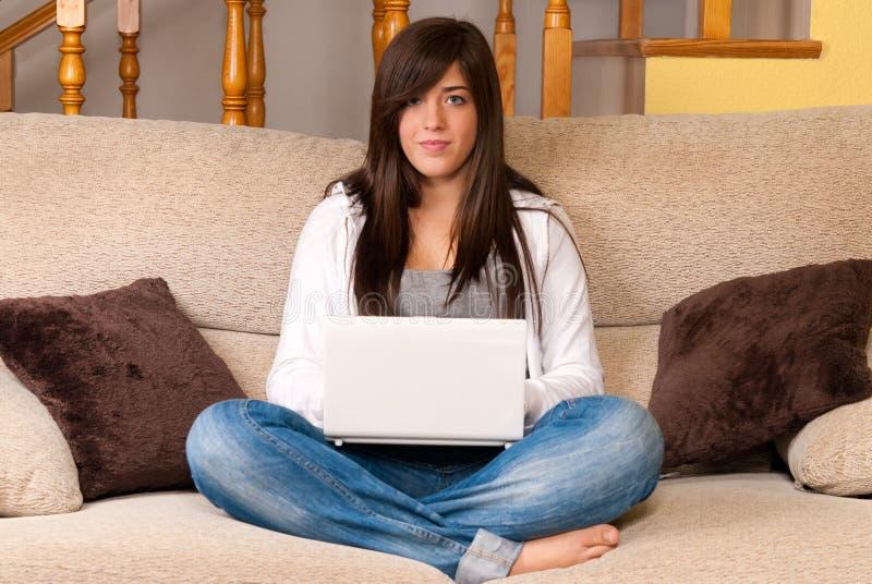 Jonge vrouw met laptop draagbare computerzitting op bank stock afbeeldingen