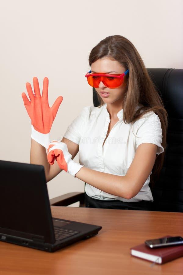 Jonge vrouw met laptop in handschoenen en sinaasappel stock afbeeldingen