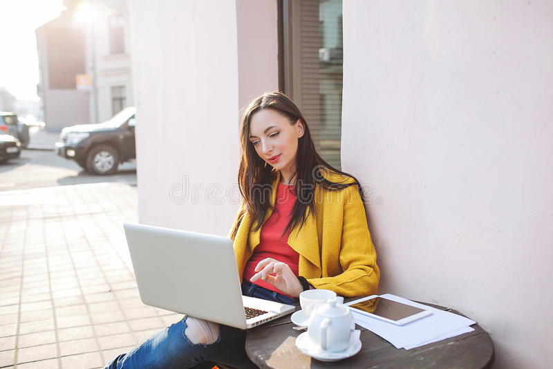 Jonge vrouw met laptop tablet en thee in openlucht in koffie royalty-vrije stock afbeeldingen