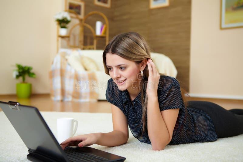 Jonge vrouw met laptop thuis royalty-vrije stock foto's