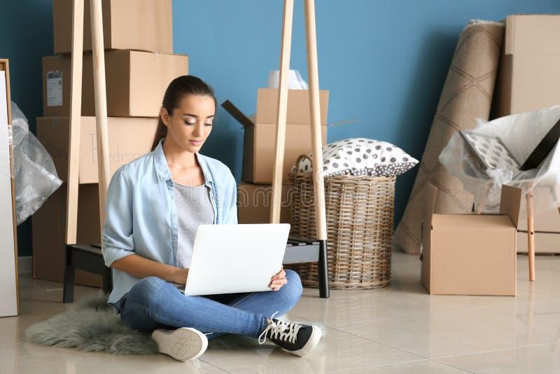 Jonge vrouw met laptop zitting op vloer dichtbij dozen en bezittingen binnen Het bewegen zich in Nieuw Huis royalty-vrije stock foto's