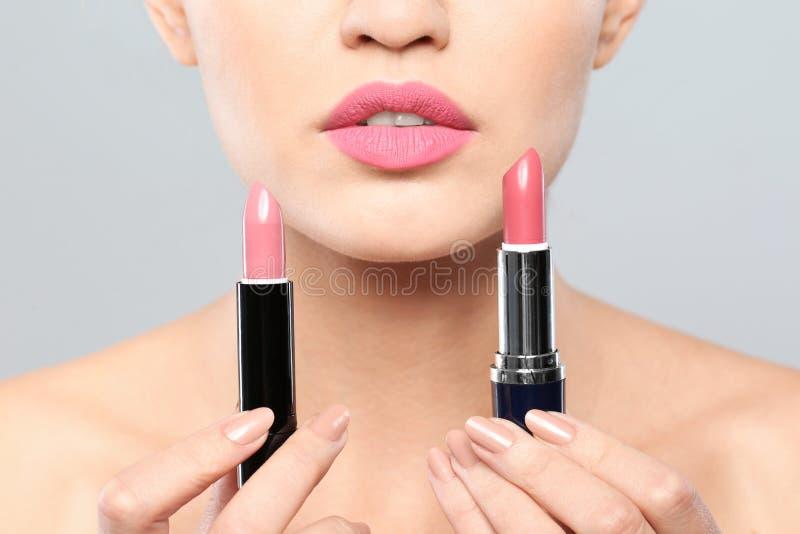 Jonge vrouw met lippenstiften op grijze achtergrond stock afbeeldingen
