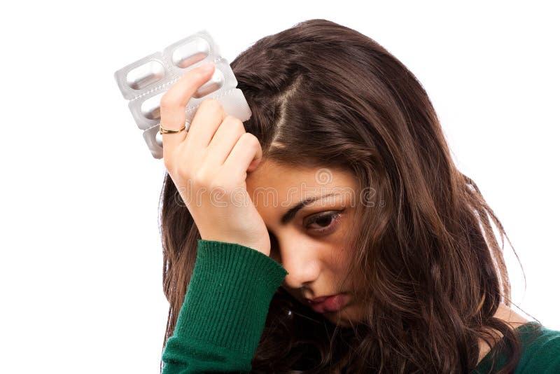 Jonge vrouw met migraine, die pillen houdt royalty-vrije stock afbeelding
