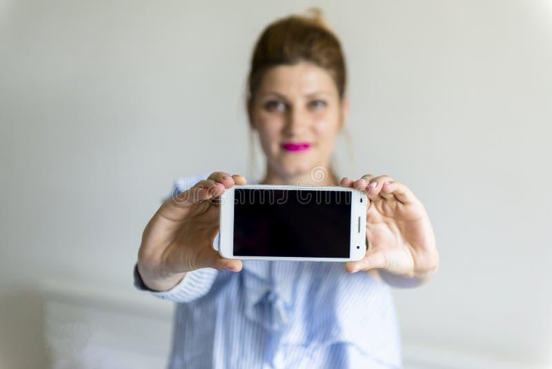 Jonge vrouw met mobiele telefoon stock afbeeldingen