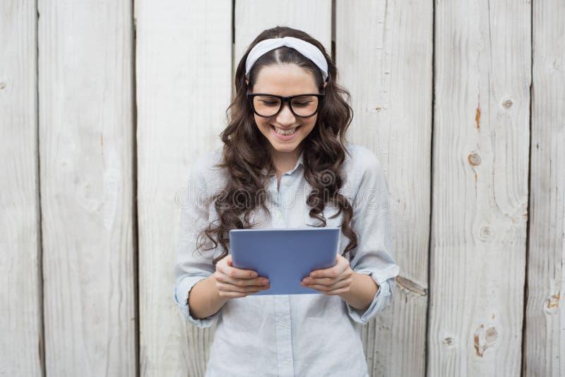 In jonge vrouw met modieuze glazen die haar tablet gebruiken stock afbeeldingen