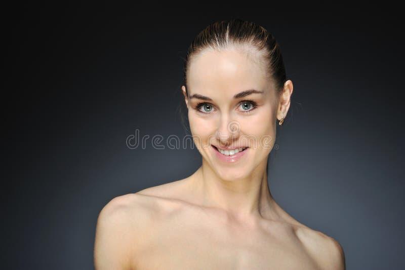 Jonge vrouw met mooi gezond gezicht - donkere achtergrond stock fotografie