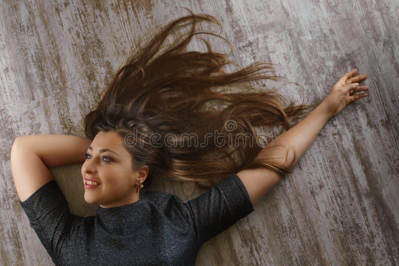 Jonge vrouw met mooi kapsel die op de vloer liggen Hoogste mening stock foto