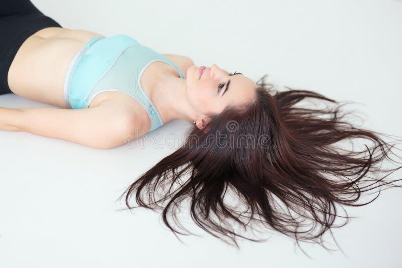 Jonge vrouw met mooi kapsel die sportkleding dragen die op de vloer liggen royalty-vrije stock foto