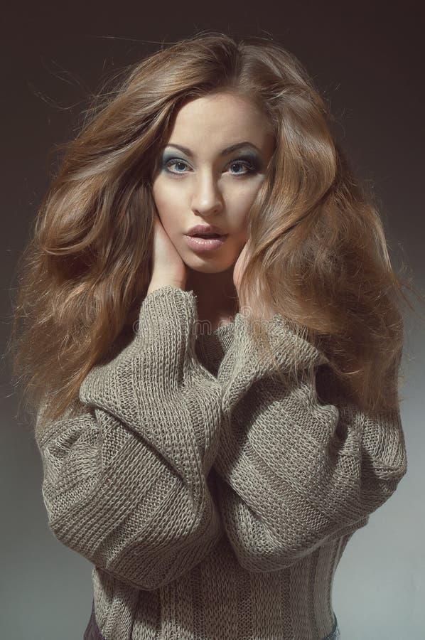 Jonge vrouw met mooi lang haar in gebreid stock foto