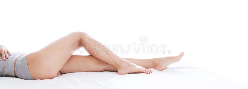 Jonge vrouw met mooie lange benen op witte achtergrond, close-up, meisje op bed stock foto's
