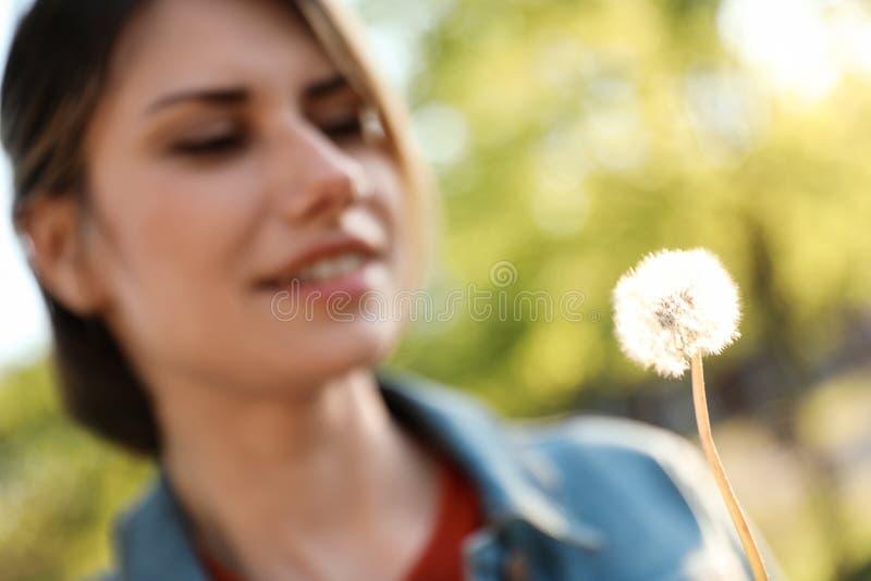 Jonge vrouw met paardebloem in park op zonnige dag Allergie vrij concept royalty-vrije stock afbeeldingen