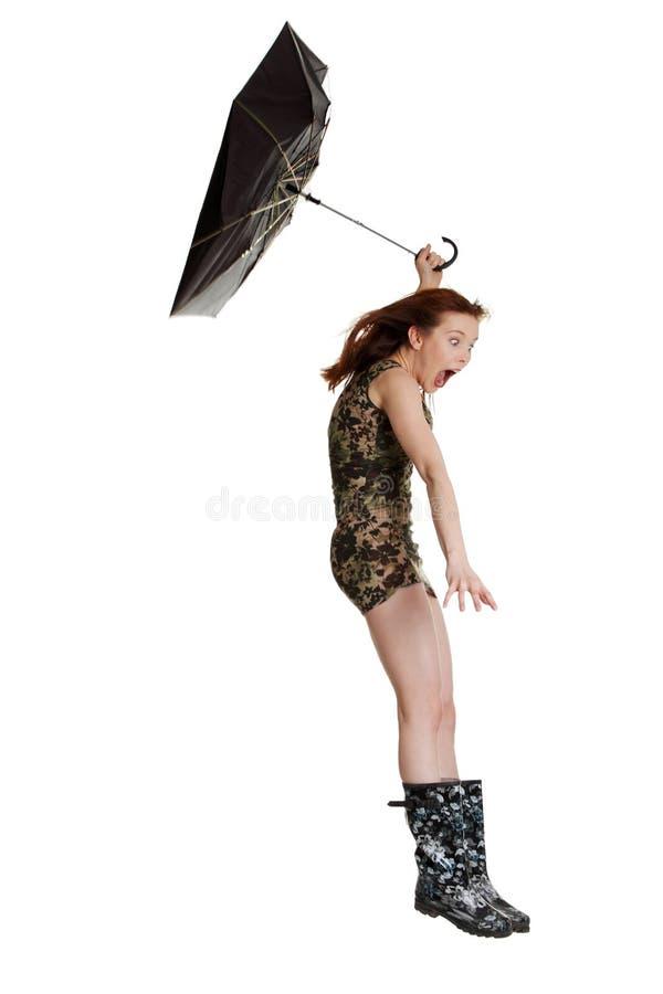 Jonge vrouw met paraplu die door wind wordt geblazen. stock foto