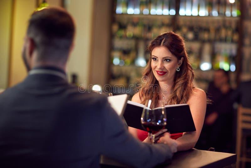 Jonge vrouw met partner in restaurant stock afbeelding