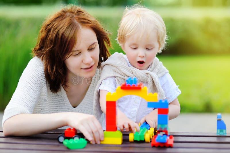 Jonge vrouw met peuterzoon het spelen met plastic blokken royalty-vrije stock foto's