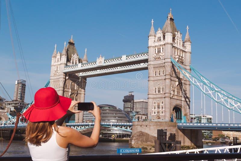 Jonge vrouw met rode hoed die een foto van de Torenbrug nemen in Londen stock afbeelding