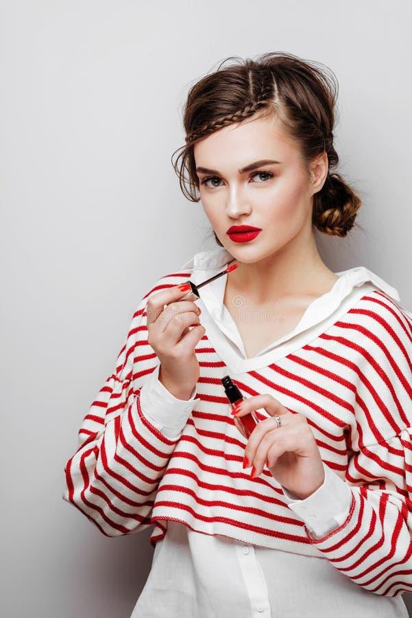 Jonge vrouw met rode lippen op vrij emotioneel gezicht in elegante de make-uplippenstift van de kledingsholding in studio royalty-vrije stock fotografie