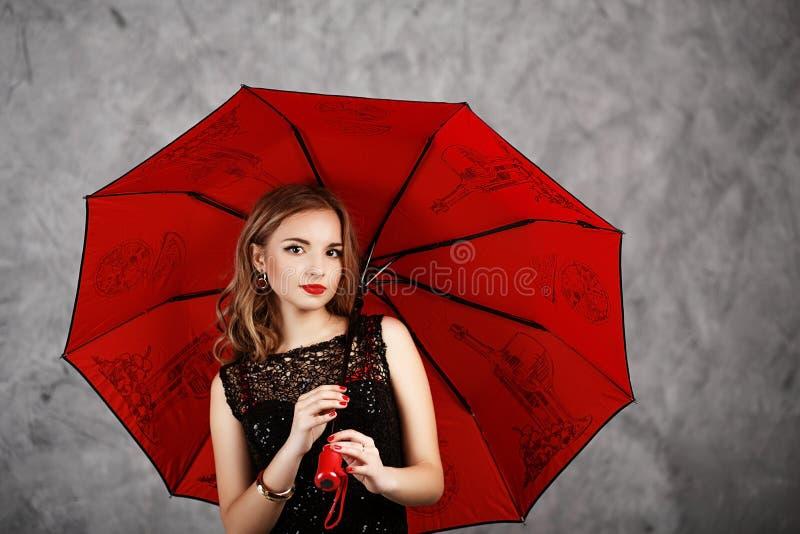 Jonge vrouw met rode paraplu stock afbeelding