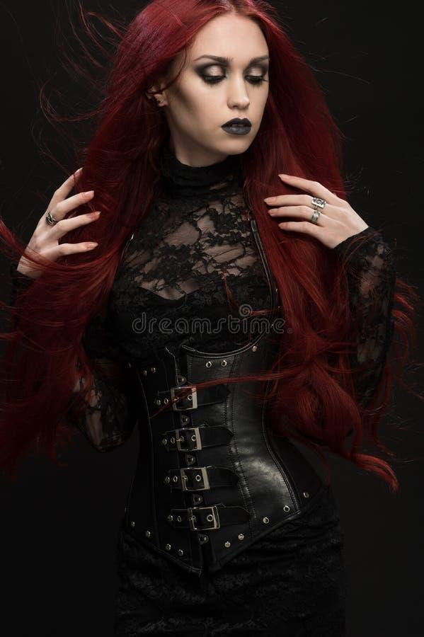Jonge vrouw met rood haar in zwart gotisch kostuum royalty-vrije stock foto