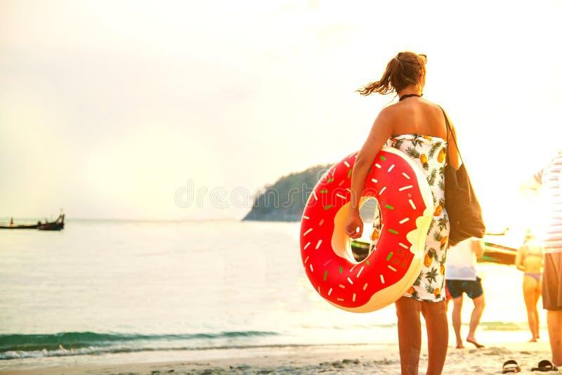 Jonge vrouw met roze cirkel die zich op het strand bevinden Op zee de zomervakantie stock afbeelding