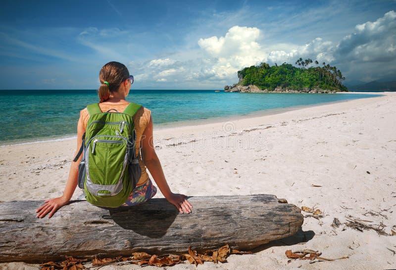 Jonge vrouw met rugzak het ontspannen op kust en het kijken aan een isl royalty-vrije stock fotografie