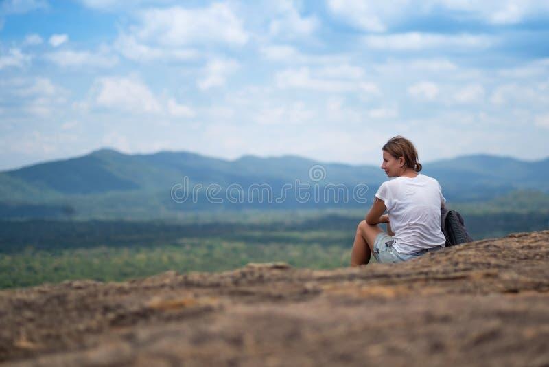 Jonge vrouw met rugzakzitting op berg en het kijken aan een hemel met wolken royalty-vrije stock afbeelding