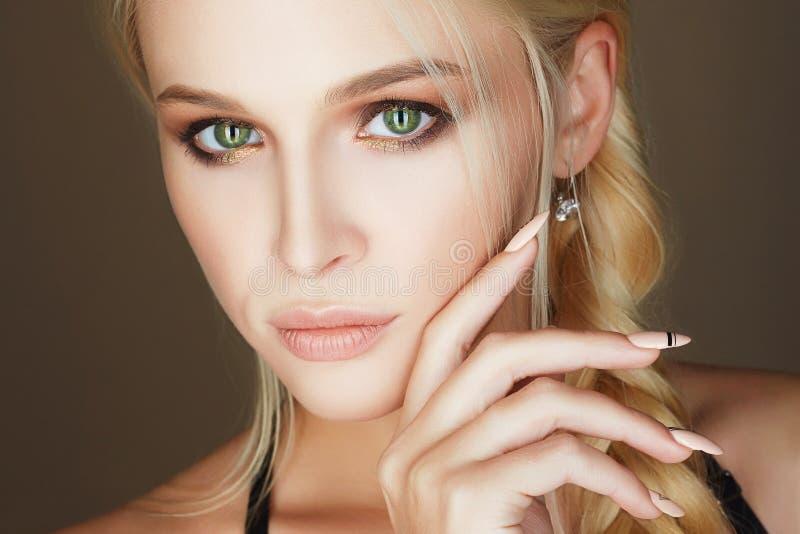 Jonge vrouw met samenstelling en manicurespijkers stock afbeelding