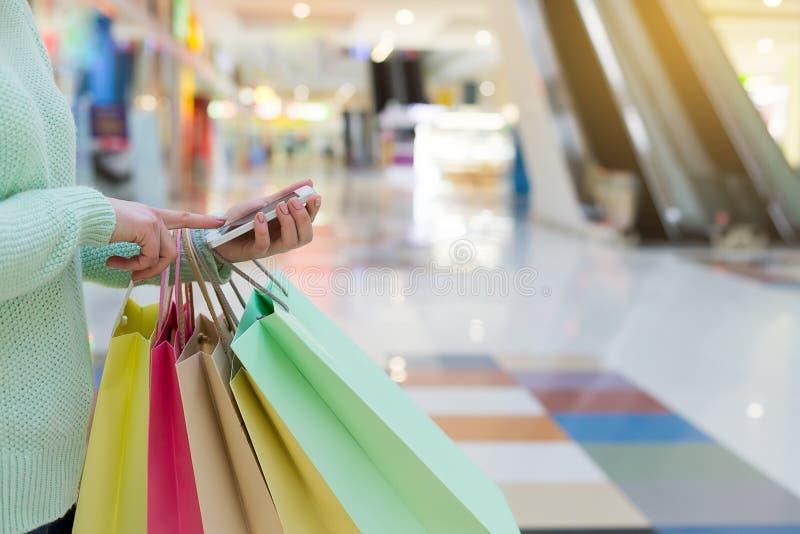 Jonge vrouw met smartphone en kleurrijke zakken in winkelcomplex stock foto