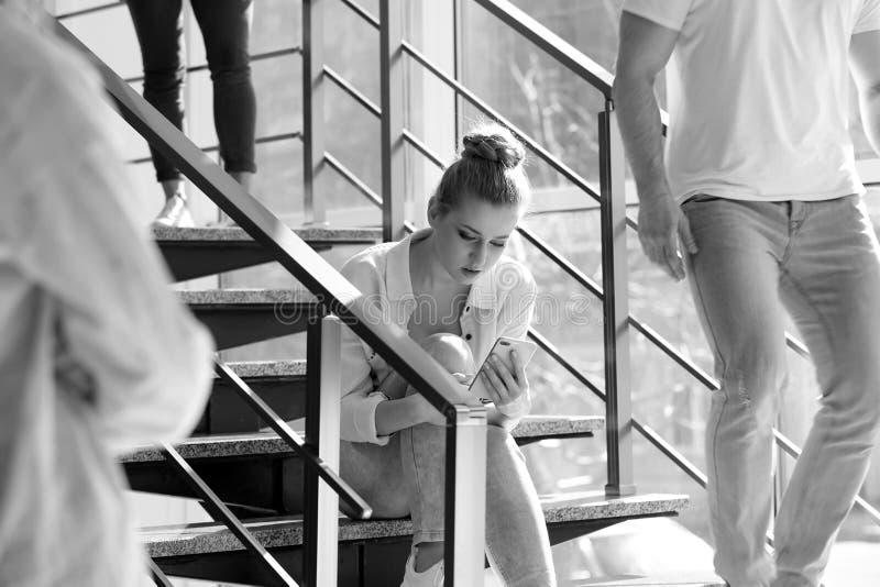 Jonge vrouw met smartphonezitting op treden, die in zwart-wit worden gestemd royalty-vrije stock fotografie