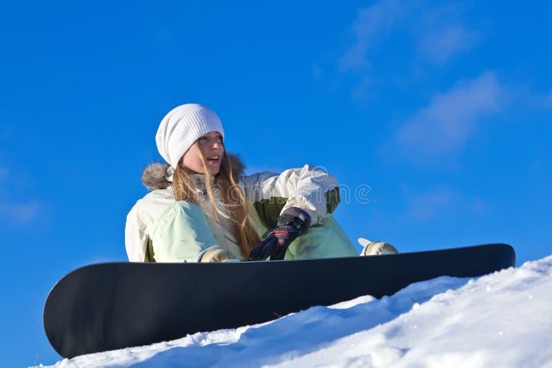 Jonge vrouw met snowboard op een helling stock fotografie