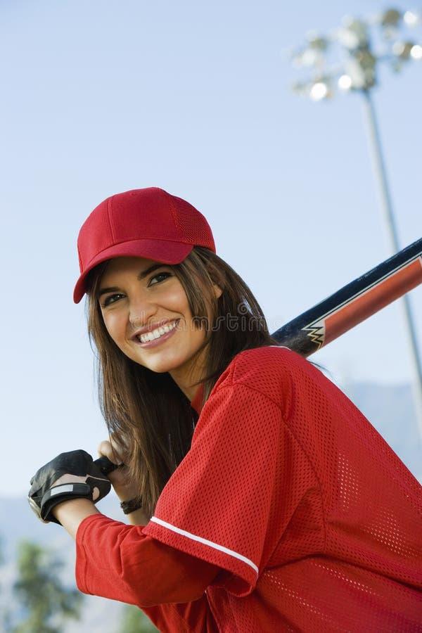 Jonge vrouw met softballknuppel stock fotografie