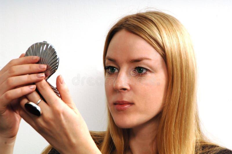 Jonge vrouw met spiegel stock foto