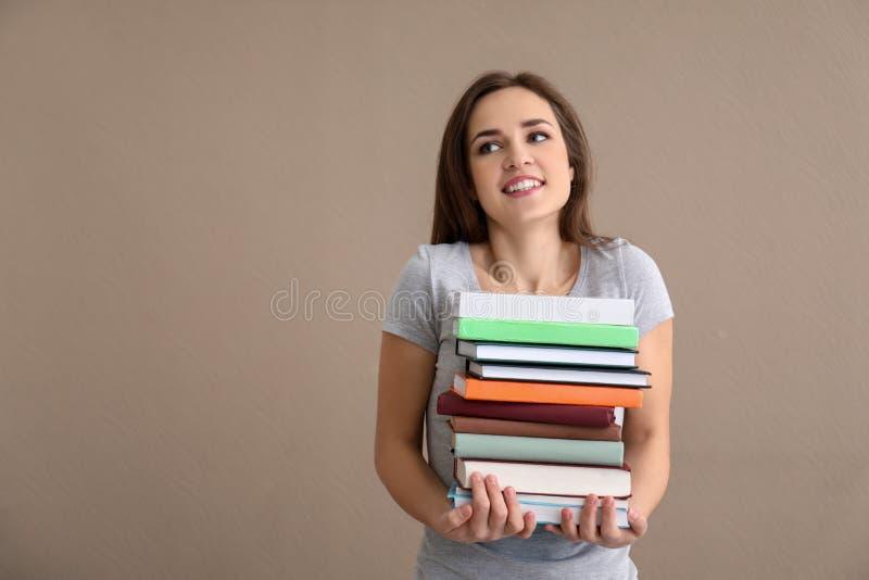 Jonge vrouw met stapel boeken op kleurenachtergrond stock fotografie