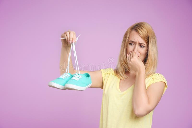 Jonge vrouw met stinky schoenen op kleurenachtergrond royalty-vrije stock fotografie