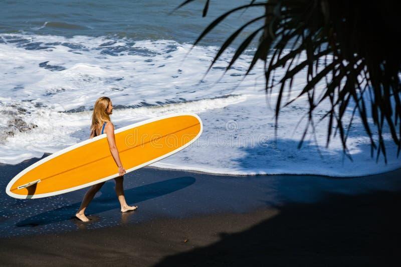 Jonge vrouw met surfplankgang op zwart zandstrand royalty-vrije stock afbeelding