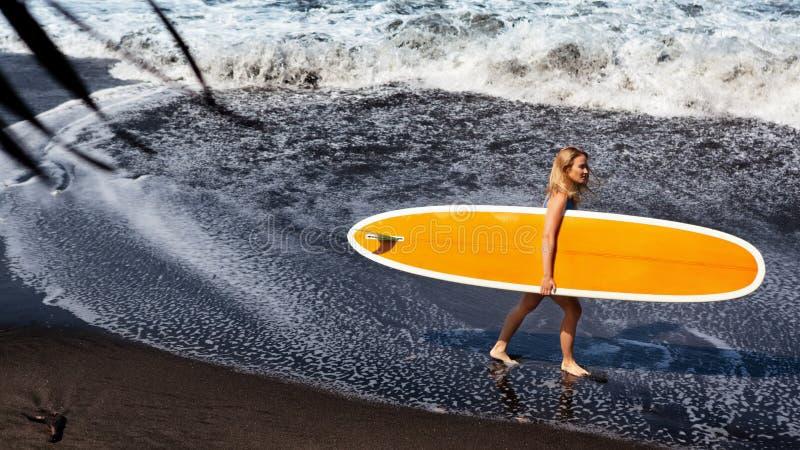 Jonge vrouw met surfplankgang op zwart zandstrand royalty-vrije stock fotografie