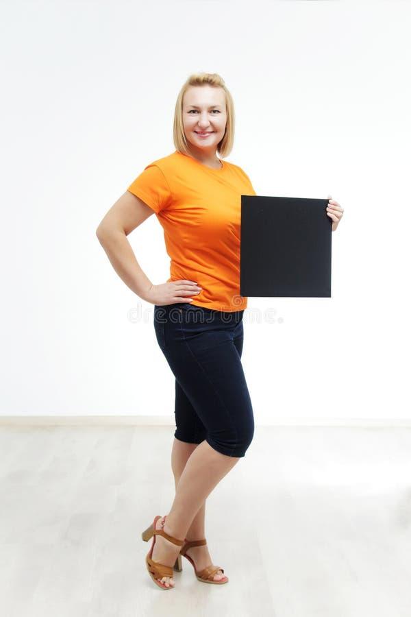 Jonge vrouw met teken houdt zij tegen een witte achtergrond stock afbeelding