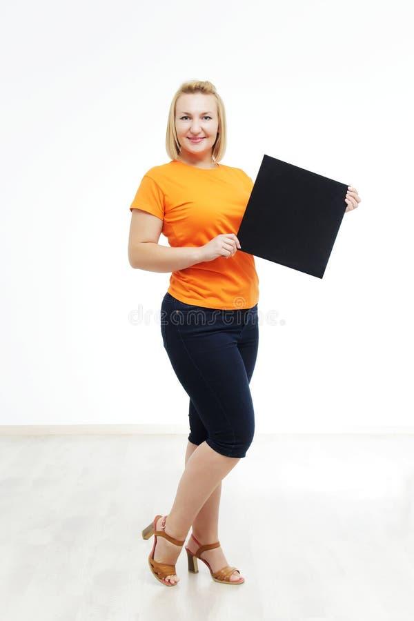 Jonge vrouw met teken houdt zij tegen een witte achtergrond stock foto's
