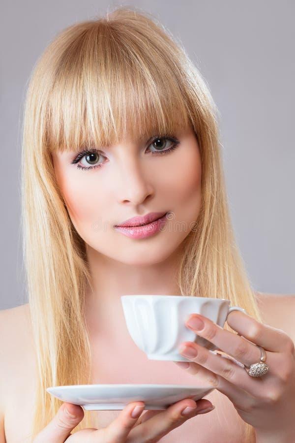 Jonge vrouw met thee stock foto