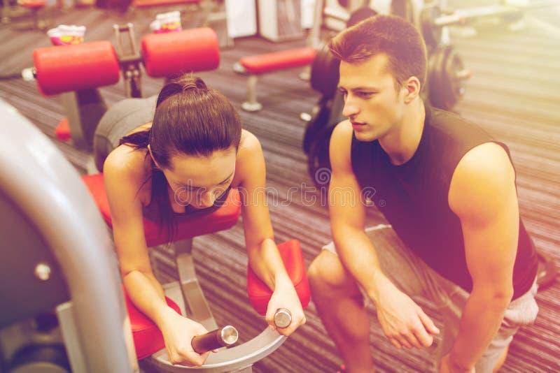 Jonge vrouw met trainer het uitoefenen op gymnastiekmachine stock afbeeldingen