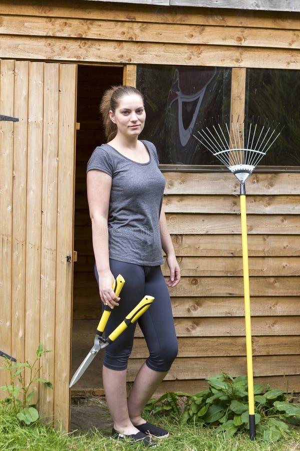 Jonge vrouw met tuin pruner en hark royalty-vrije stock afbeelding