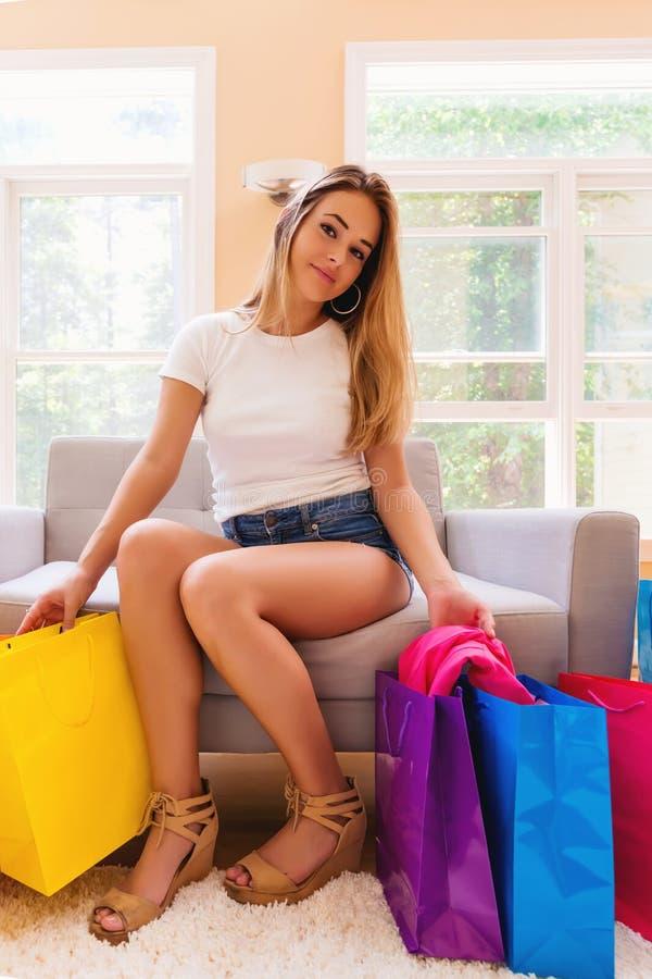 Jonge vrouw met vele helder gekleurde het winkelen zakken stock afbeeldingen