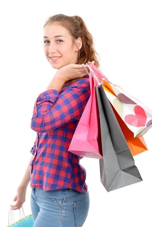 Jonge vrouw met vele het winkelen zakken op witte achtergrond stock foto's