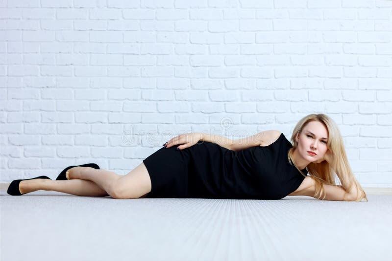 Jonge vrouw met verdacht gezicht in het zwarte kleding stellen bij de vloer stock foto's