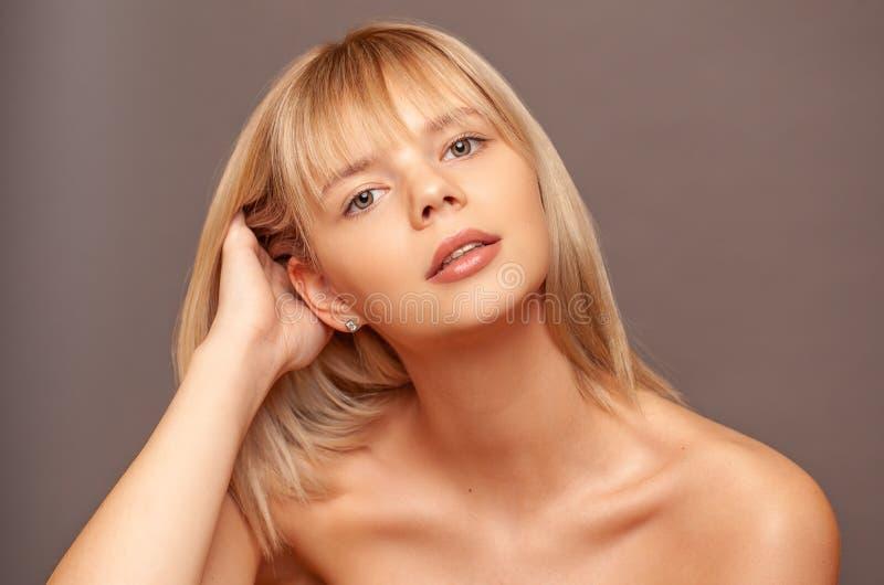 Jonge vrouw met verse gezonde huid en haren wat betreft haar gezicht De kosmetiek, schoonheid en kuuroord Grijze achtergrond stock fotografie