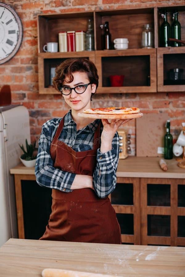Jonge vrouw met verse pizza bij haar keuken royalty-vrije stock afbeeldingen