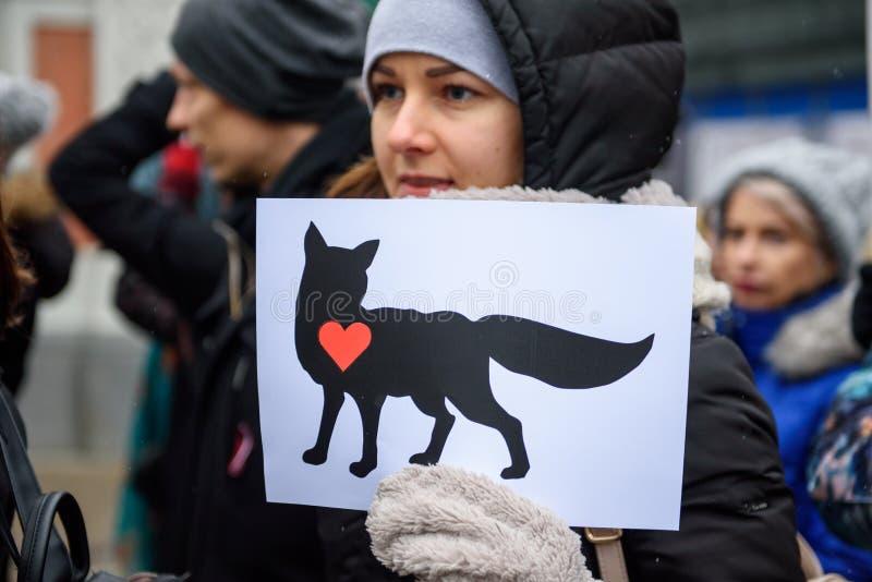 Jonge vrouw met vossymbool prinet op Witboek bij handen, in 'Maart voor dieren in Riga, Letland royalty-vrije stock fotografie