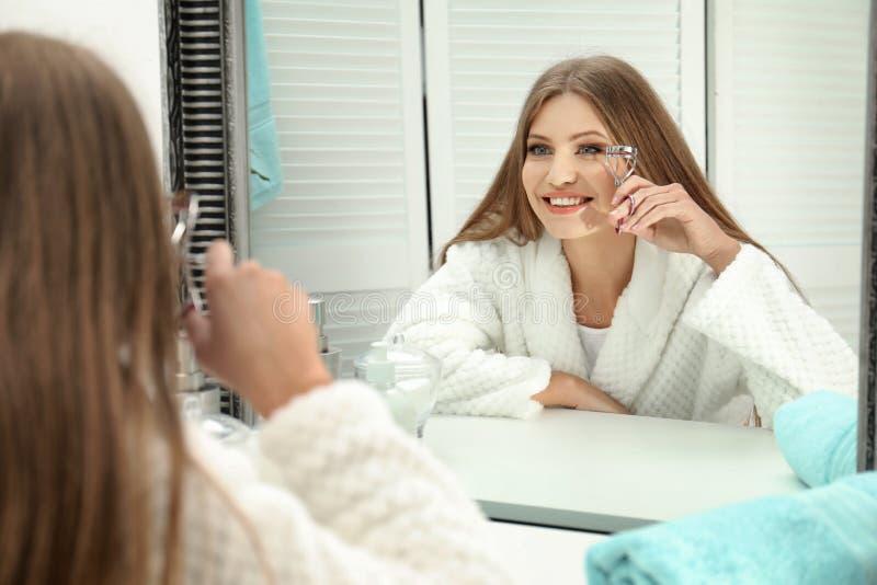 Jonge vrouw met wimperkrulspeld dichtbij spiegel stock foto's