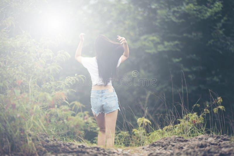 Jonge vrouw met winderig slordig haar backlit door zon selectieve nadruk stock afbeelding