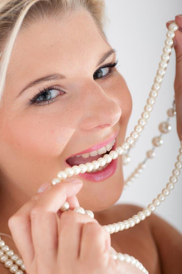 Jonge vrouw met witte gezonde tanden en parels stock foto's