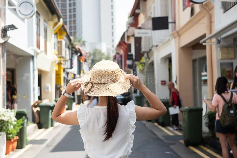 Jonge vrouw met witte kleding en hoed reizen, gelukkige Aziatische reiziger in Haji Lane lopen en Arabische straat die in Singapo royalty-vrije stock foto